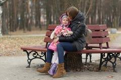 La mamá y la hija se están sentando en un banco de parque imagen de archivo