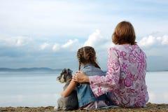 La mamá y la hija sientan el abarcamiento en el lago y miran el agua Fotografía de archivo