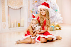La mamá y la hija vestidas como Papá Noel celebran la Navidad Familia en Fotos de archivo