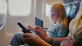 La mamá y la hija vuelan en el avión, utilizan la tableta y el teléfono Tecnología en el camino almacen de metraje de vídeo
