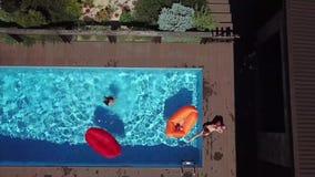 La mamá y las hijas están descansando sobre la piscina almacen de metraje de vídeo
