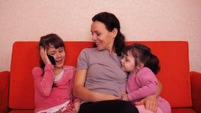 La mamá y las hijas juegan con un teléfono móvil Familia feliz que juega en teléfono móvil almacen de video