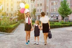 La mamá y los niños que llevan a cabo las manos, van a la escuela Fotos de archivo libres de regalías