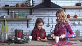 La mamá y la pequeña hija en camisas de tela escocesa desayunan en la cocina que comen galletas y un té de consumición junto almacen de metraje de vídeo