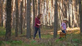 La mamá y la pequeña hija van en el camino en el bosque del otoño que prolifera rápidamente el frunce de la familia y las bayas e almacen de metraje de vídeo