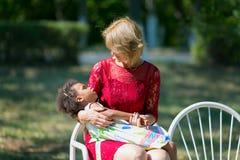 La mamá y su hija adoptada se están sentando en el banco imagen de archivo libre de regalías