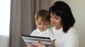 La mamá y su niño pasan tiempo en la tableta en casa, jugando y mirando las historietas, jugando a los videojuegos, usando metrajes