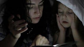 La mamá y su pequeña hija están leyendo los cuentos de hadas para la noche, las envuelven en una manta caliente y se sumergen ade almacen de video