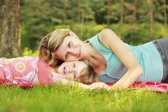 La mamá y su pequeña hija mienten en la hierba imágenes de archivo libres de regalías