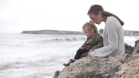 La mamá y su pequeña hija se están sentando en las rocas por el mar y hablar almacen de metraje de vídeo
