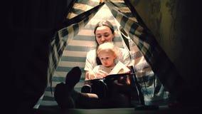 La mamá y su pequeño bebé leyeron un libro juntos en una tienda de los indios norteamericanos por la tarde metrajes