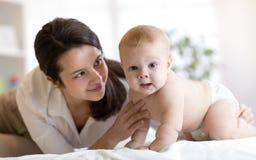 La mamá y su pequeño hijo weared el pañal en cama Bebé infantil de abarcamiento de la madre Imágenes de archivo libres de regalías