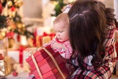 La mamá y un niño pequeño están jugando cerca del árbol de navidad por el Año Nuevo Historia de la Navidad Imagen de archivo libre de regalías
