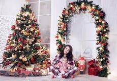 La mamá y un niño pequeño están jugando cerca del árbol de navidad por el Año Nuevo Historia de la Navidad Imagen de archivo