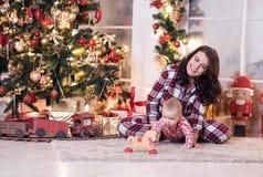 La mamá y un niño pequeño están jugando cerca del árbol de navidad por el Año Nuevo Historia de la Navidad Imagenes de archivo