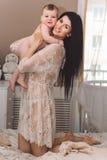 La mamá bastante feliz y el pequeño hijo están mintiendo en cama Fotos de archivo
