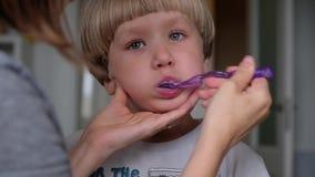 La mam? del primer ayuda a limpiar los dientes a su peque?o hijo por la ma?ana Hijo de ayuda de la madre cepillar sus dientes almacen de video
