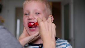La mam? del primer ayuda a limpiar los dientes a su peque?o hijo por la ma?ana Malos dientes almacen de metraje de vídeo