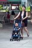 La mamá feliz trae al niño con los paseos del cochecito en parque Foto de archivo