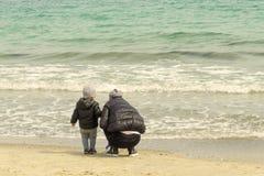 La mam? y el ni?o en la costa recogen c?scaras imagen de archivo libre de regalías