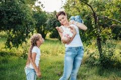 La mam? y sus hijas est?n caminando en el parque del verano foto de archivo libre de regalías