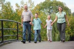 La mama, el papá, el hijo y la hija está recorriendo en el puente Foto de archivo
