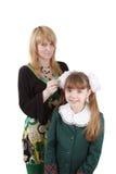 La mama está aplicando el pelo de la colegiala con brocha joven. Fotografía de archivo