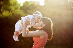 La mama mantiene a la hija sus brazos Imagenes de archivo