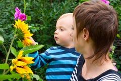 La mama muestra las flores del hijo en jardín Fotografía de archivo