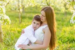 La maman étreint doucement son fils dans les rayons du coucher de soleil Photographie stock libre de droits