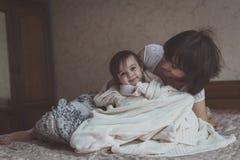 La maman étreint et joue avec son cache-cache de fille sur le lit, la vie images stock