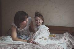 La maman étreint et joue avec son cache-cache de fille sur le lit, la vie image stock