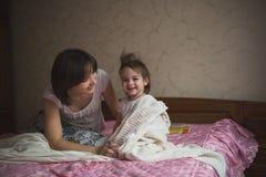 La maman étreint et joue avec son cache-cache de fille sur le lit, la vie photographie stock libre de droits