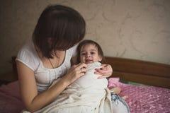 La maman étreint et joue avec son cache-cache de fille sur le lit, la vie photo stock