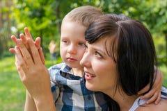 La maman étreint et tient une main dans sa main du ` s de fils Photos libres de droits