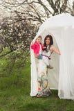 La maman étreint la fille de baisers dans le jardin luxuriant de ressort Images stock