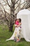 La maman étreint la fille de baisers dans le jardin luxuriant de ressort Photo stock