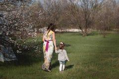 La maman étreint la fille de baisers dans le jardin luxuriant de ressort Photos libres de droits