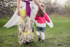 La maman étreint la fille de baisers dans le jardin luxuriant de ressort Photo libre de droits