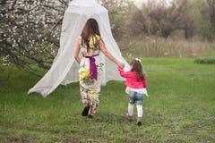 La maman étreint la fille de baisers dans le jardin luxuriant de ressort Photographie stock libre de droits