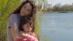 La maman étreint sa fille par la rivière Une petite fille avec sa mère par l'eau Famille en plein air banque de vidéos