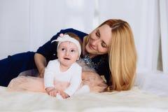 La maman étreint sa petite fille qui essaye de lui dire les premiers mots Une femme regarde son enfant avec amour Images stock