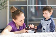 La maman affectueuse européenne essaye de réparer la voiture de jouet, passe le temps gratuit avec son fils, fait attention, essa photos stock