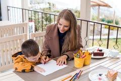 La maman aide le fils à dessiner les crayons colorés par dessin Image stock