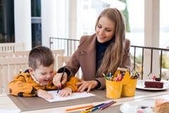 La maman aide le fils à dessiner les crayons colorés par dessin Photographie stock libre de droits