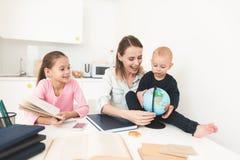 La maman aide ma fille à faire ses devoirs dans la cuisine Images libres de droits