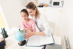 La maman aide ma fille à faire ses devoirs dans la cuisine Image stock