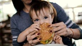 La maman alimente à l'enfant un hamburger savoureux, cheeseburger clips vidéos