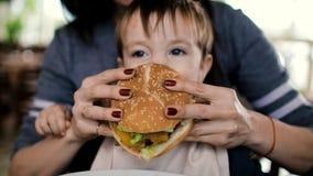 La maman alimente à l'enfant un hamburger savoureux, cheeseburger banque de vidéos