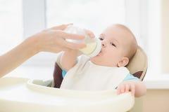 La maman alimente à son bébé une bouteille de lait photos libres de droits
